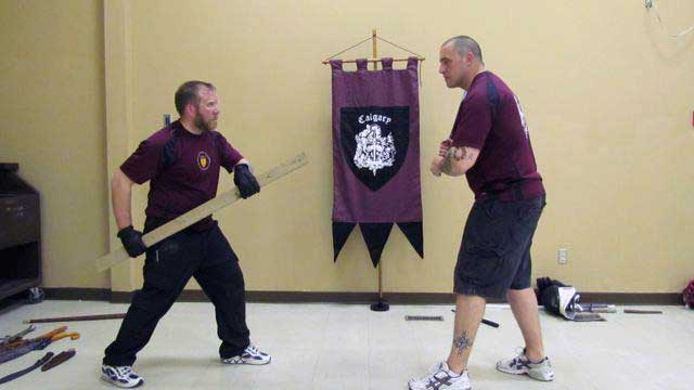 Half-swording techniques, a 2x4 length of wood vs an assailant with a bat. Start in a half-sword guard.